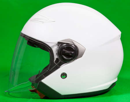 Open face white motorcycle helmet with attached face shield, side view, a green background Banque d'images