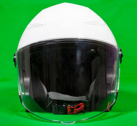 Open face white motorcycle helmet with attached face shield, front view, green background