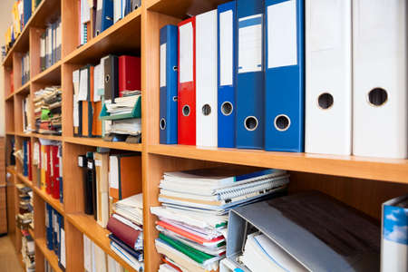 Row of colourful office folders with blank white labels on shelf