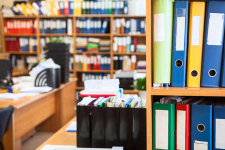 Colorful file binders are on office room shelves, copyspace with blurred background