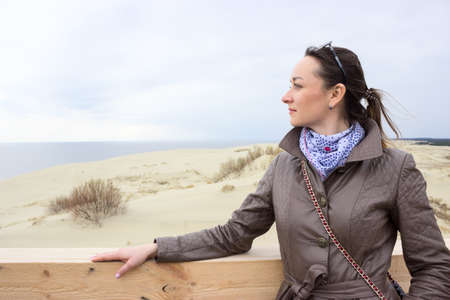 Thoughtful woman portrait, standing on tongue of sand, looking far away, copyspace