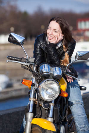 Young woman motorcyclist put out tonque at somebody while sitting bike Stock Photo