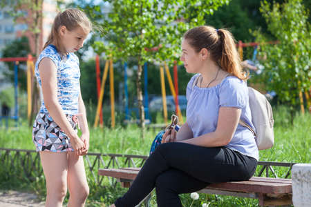 Mom blows up her young daughter for bad behavior while walking on playground Stockfoto