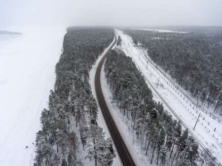 Aerial view at parallel highway and railroad range winter sea coast. Snowy blizzard weather. View from flying drone 免版税图像