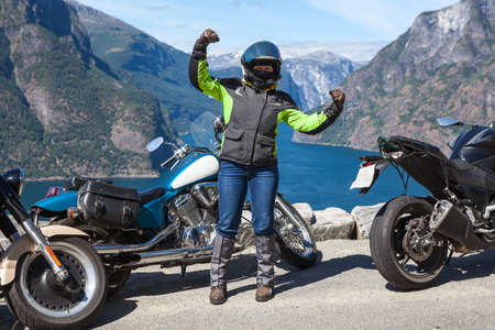 Female motorcyclist from biker group triumphs on mountain road overlooking the Norwegian fjords and nature, travel on Norway