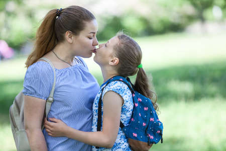 Mother kissing her daughter while walking in summer park together