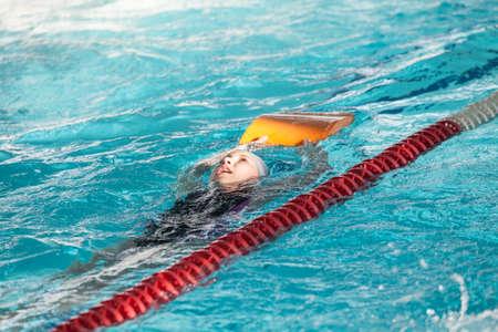Young Caucasian girl sportsman swiming backstroke with kickboard in pool