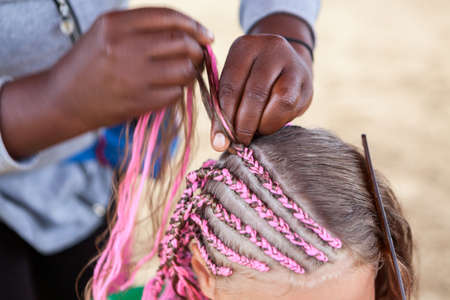 Afro American hairdresser made plaits in African style for young Caucasian girl, close up view Stok Fotoğraf
