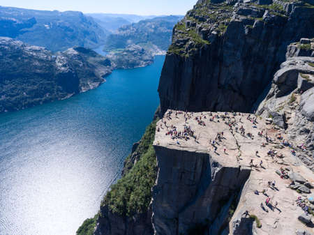 Steep rock Preikestolen over water of fjord Lysefjorden, natural attraction. Top view, flight above cliff. Preachers Pulpit or Preachers Chair is in Forsand, Norway