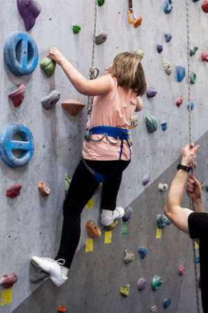 Chubby pretty Caucasian girl climbering artificial rock-climbing wall with trainer help and safety cable 免版税图像