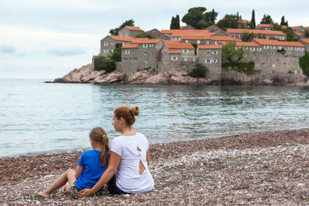Woman with her daughter resting on sea beach, sitting on earth, , Montenegro, Adriatic sea, Europa Standard-Bild - 116154128