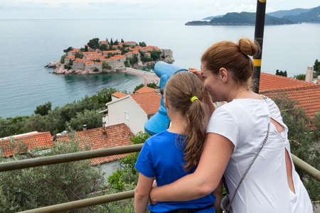 Mom and daughter looking at  island. Adriatic sea, Montenegro, Europa. Observing place with coin operated telescope in town Standard-Bild - 116619143