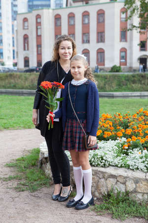 Full-length portrait of Caucasian mother and daughter going back to school together, schoolchild in uniform holding flowers Standard-Bild - 116619140