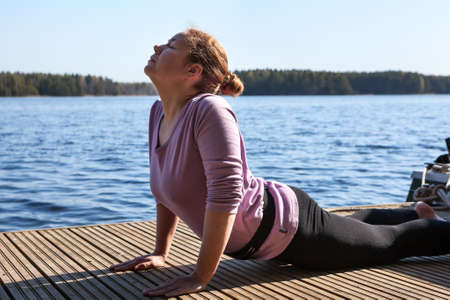 Stretching exercise at pier near the lake, yoga with breath control and simple meditation Standard-Bild - 116619141