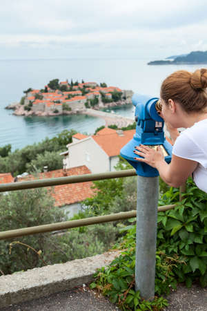 Observing place with coin operated binoculars in  town. Woman looking at island in Adriatic sea, Montenegro, Europe Standard-Bild - 116619144