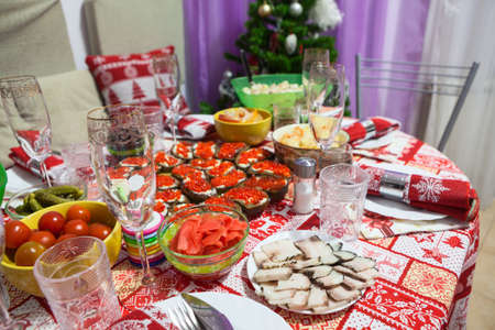 Festive table with food served with red ornament tablecloth is ready for Christmas or New Year celebration. Russia Standard-Bild - 116158700