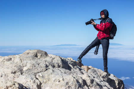 Photographer takes a picture while standing on the mountain peak at strong wind Standard-Bild - 116158701