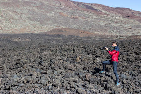 Photographer and traveller taking a picture of volcanic lava stones standing on clinker field near mountain Standard-Bild - 116158705