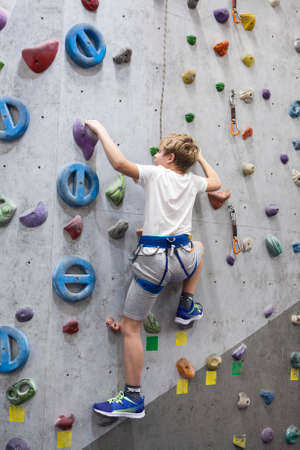 Artificial climbing facility and Caucasian boy with safety line on walls Standard-Bild - 116158748