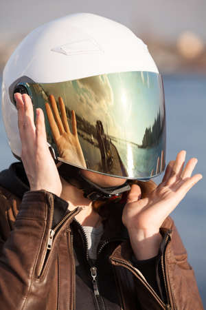 Close up portrait of unrecognizable European female motorcyclist with white open face helmet with mirrored tinted visor