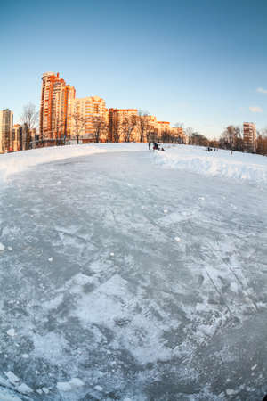 Natural empty ice rink on frozen lake in sleeping quarters of St. Petersburg at winter season. Russia Standard-Bild - 116158779