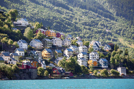 Colourful wooden houses for living on mountain slope near Norwegian fjord, Odda town, Hordaland county, Norway 版權商用圖片