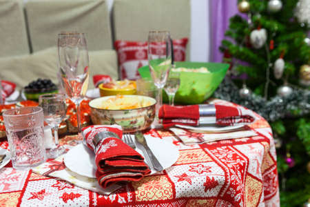 Table with food in domestic kitchen, laid and decorated for New Year celebration. Christmas tree