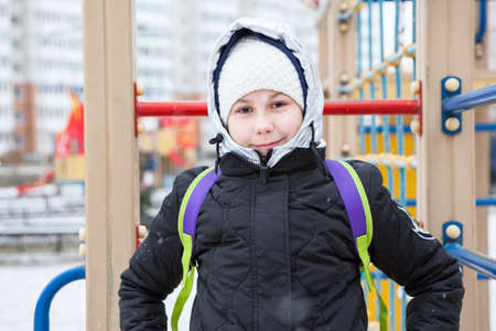 Cute European girl in winter clothes standing on children playground, puffy jacket with wool hat and hood Standard-Bild - 119428145