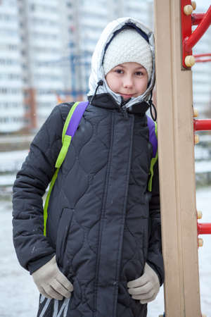 Preteen girl leaning to stairs while walking at winter cold day, portrait, looking at camera Standard-Bild - 119428147