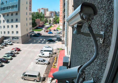 External surveillance cameras are mounted on building wall, viewing parking lot, summer