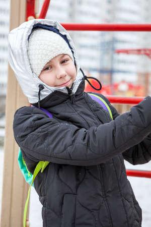 Smiling preteen girl dressed in down jacket with silver hood, woollen white hat is outdoor at winter season Standard-Bild - 119428162