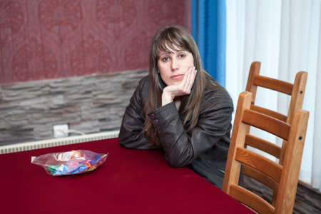 Young Caucasian woman sitting at table in room, dressed with leather brown jacket, looking at camera Standard-Bild - 119428182
