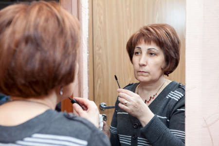 Mature woman looking in mirror and applying make up in home Standard-Bild - 119428184