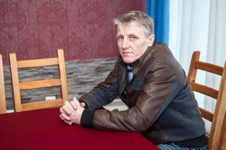 Mature Caucasian man sitting at table in room, dressed with leather brown jacket, looking at camera Standard-Bild - 119428185