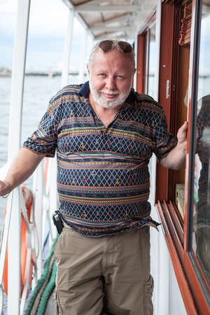 Senior Caucasian man standing on deck of own yacht, portrait, white beard and blond hairs, looking at camera Standard-Bild - 119428191