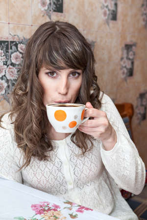 Young woman drinking tea from big mug, sitting in kitchen at table, looking at camera Standard-Bild - 119428193