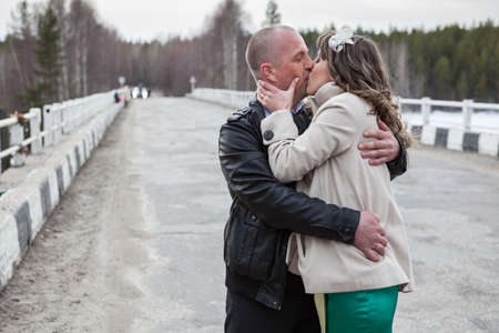 Young Caucasian guy passionately kisses his girl while standing on the road together, embracing together Standard-Bild - 119429062