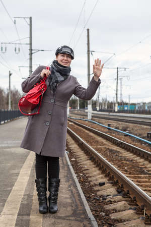 Young woman sees off her friend and waving on platform of railroad station, red bag in shoulder Standard-Bild - 119429065