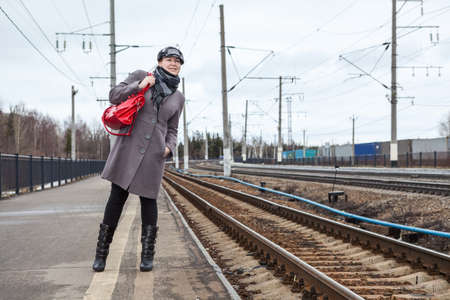 Young woman dressed coat and cap watch the train while standing on station platform, red bag in hand Standard-Bild - 119429073