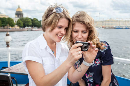Happy and smiling young European women looking on camera screen at pictures Standard-Bild - 119429075
