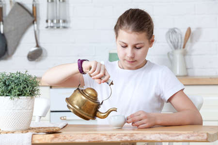 Young Caucasian girl pouring tea from small copper antique teapot into cup at kitchen Standard-Bild - 119429076