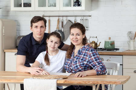 Father, mother with daughter sitting at the table in kitchen together, portrait Standard-Bild - 119429077