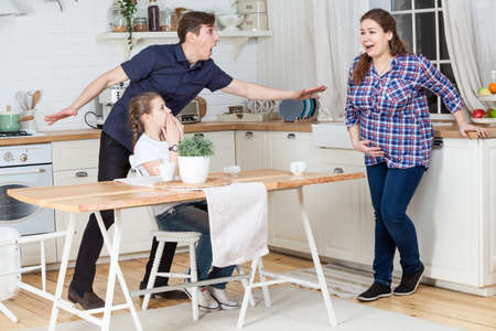 Husband and daughter are frightened of wife contractions of false labor. Family rush over at domestic kitchen Standard-Bild - 119429078