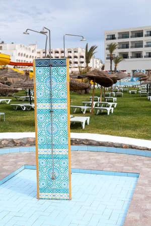 Three units shower is on sunbathing area of a hotel, green grass and sunbeds arranged around Standard-Bild - 119429102
