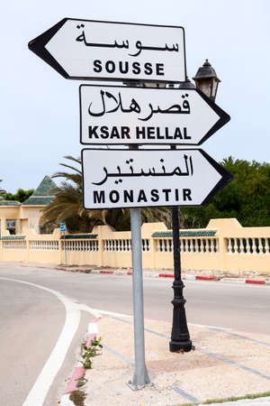 Road sign with directions to Monastir, Sousse and Ksar Hellal is in town of Tunisia. English and Arabic inscriptions. The Africa Standard-Bild - 119429116