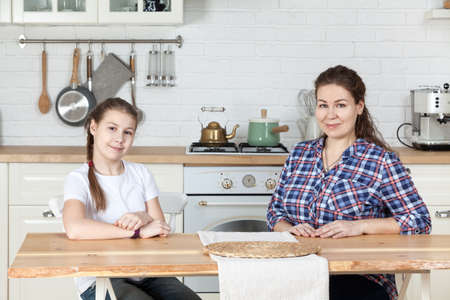Portrait of mother with her adolescent daughter sitting at the table in kitchen, looking at camera Standard-Bild - 119429121