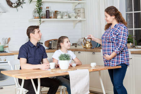 Pregnant wife with teapot preparing breakfast to husband and teen age daughter at kitchen Standard-Bild - 119429125