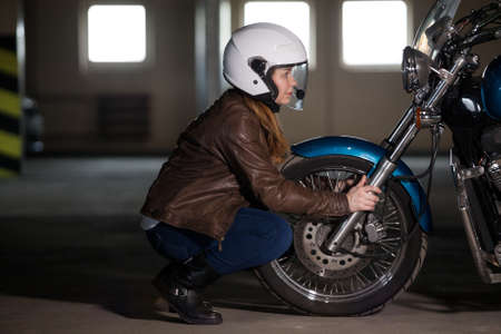 Woman motorcyclist sitting opposite of wheel of chopper bike, making inspection before riding Standard-Bild - 119431593