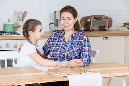 Mother and her ten years old daughter sitting together at the table in kitchen, woman looking at camera, girl embracing her mom Standard-Bild - 119431597