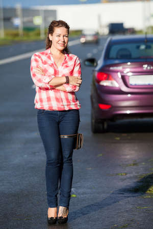 European woman dressed in shirt and blue jeans standing on the road before parked car, full length portrait Standard-Bild - 119431577